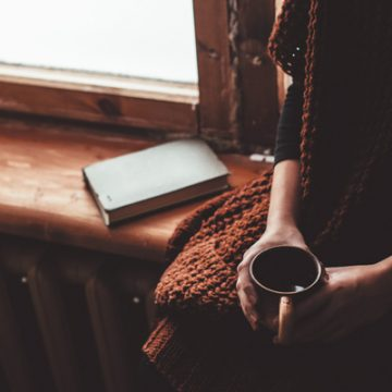 Woman sitting in silence with a cup of coffee and a book