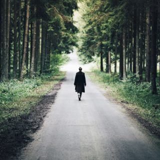 Woman walking on a road in the forest | thecozyapron.com
